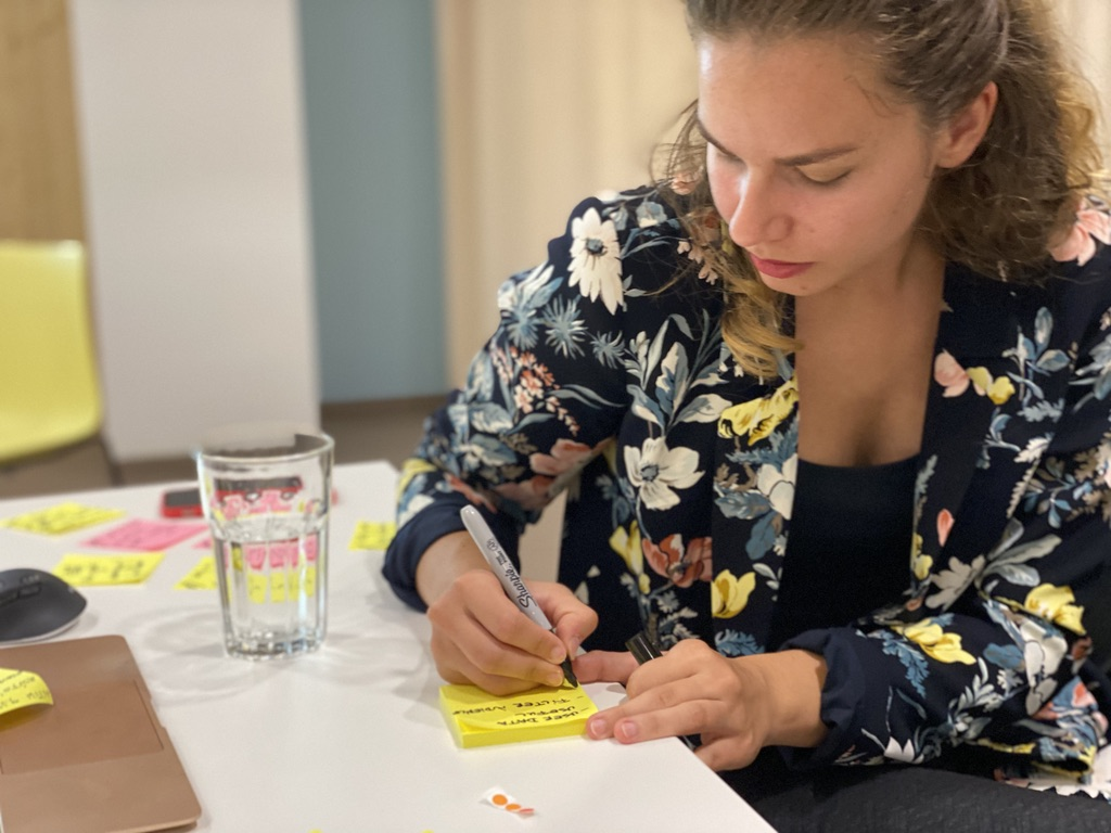 Woman writing down ideas on a Post It note